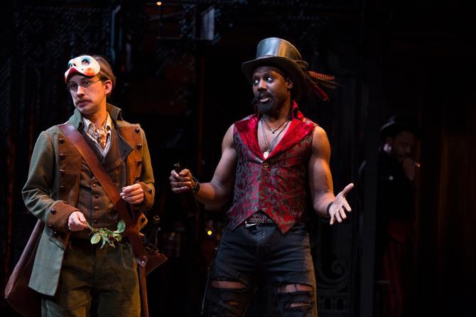A man with a mask and a man with a top hat and red waistcoat