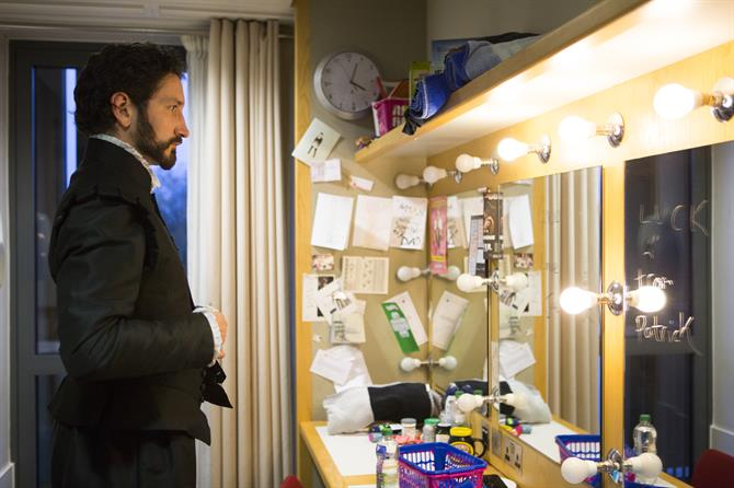 A young actor looks into a mirror surrounded by lights and cards