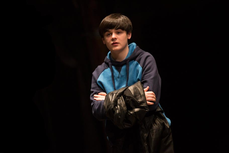 A boy with dark hair wears a blue hoodie and carries a black leather coat.