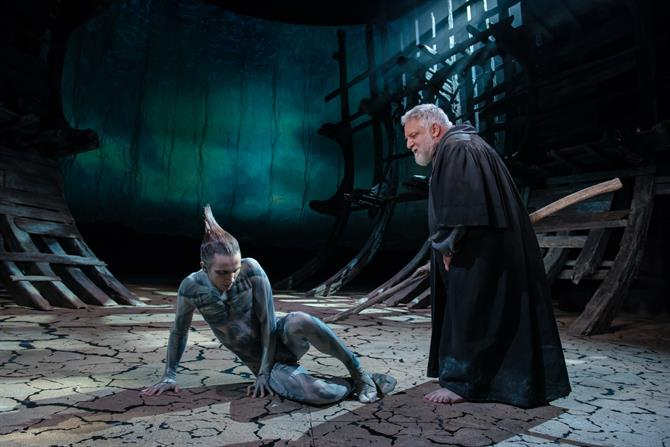 Ariel on the floor looking down while Prospero is stood over him
