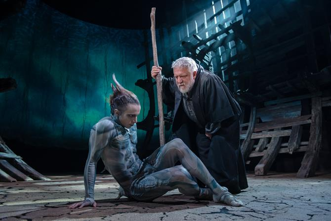 Ariel on the floor looking down with Prospero crouched down over him