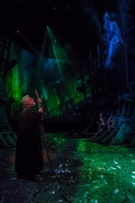 Prospero looking up at the projection of Ariel