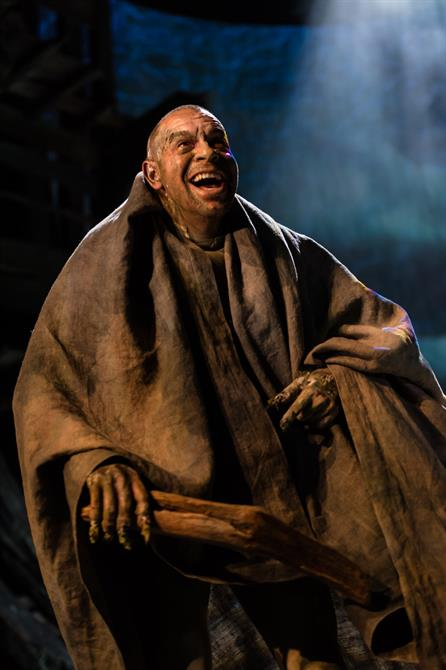 Caliban laughing with sticks in his hand