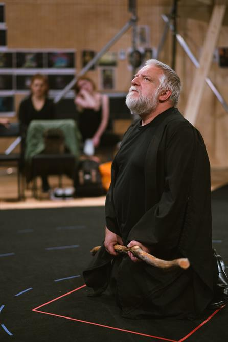 Simon Russell Beale knelt down with staff in hand