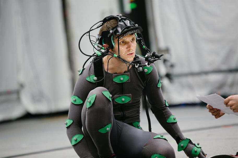 actor Mark Quartley in a headset and black motion capture suit with green eye-shapes and white dots in the centre of each one