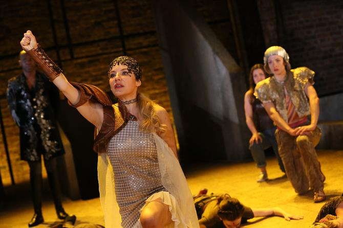 Allison McKenzie as Hippolyta with her arm in the air