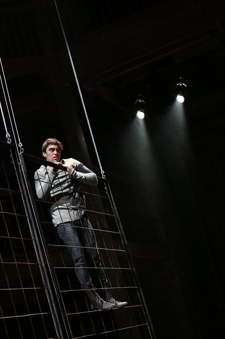 James Corrigan as Palamon climbing on the metal bars