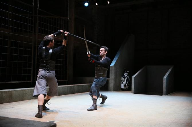 Jamie Wilkes as Arcite and James Corrigan as Palamon fighting with swords