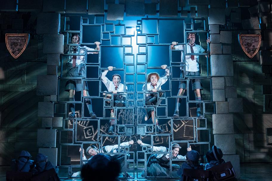 The Matilda cast in school uniform climbing on stage