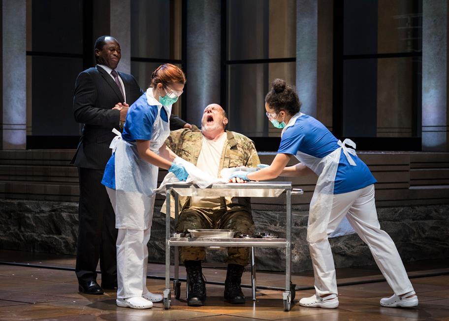 Two nurses hold down Titus as they prepare to cut off his hand. A man looks on, horrified.