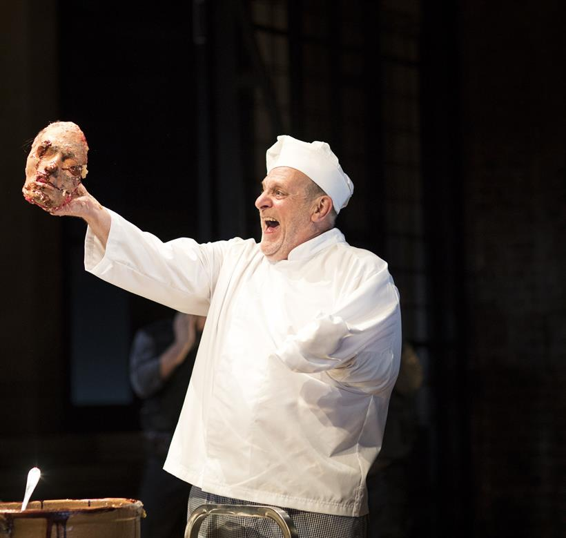 A man in chef whites holds the cast of a human face in one hand. His other arm is missing.