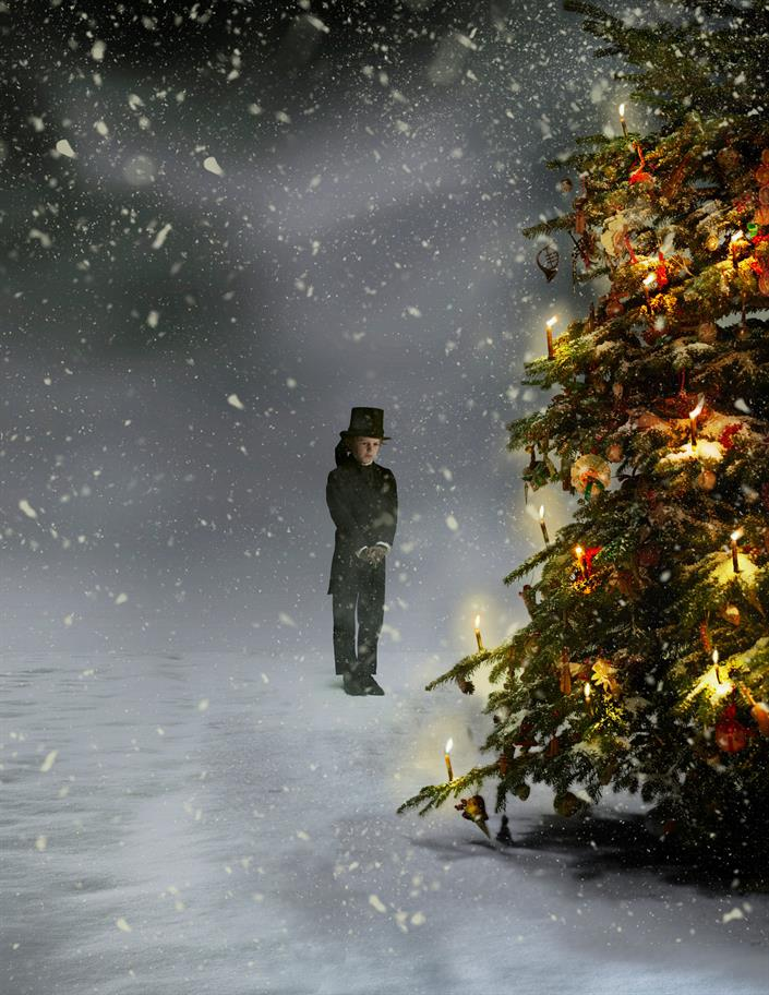 A boy standing in the snow in top hat and tails looking at a Christmas tree