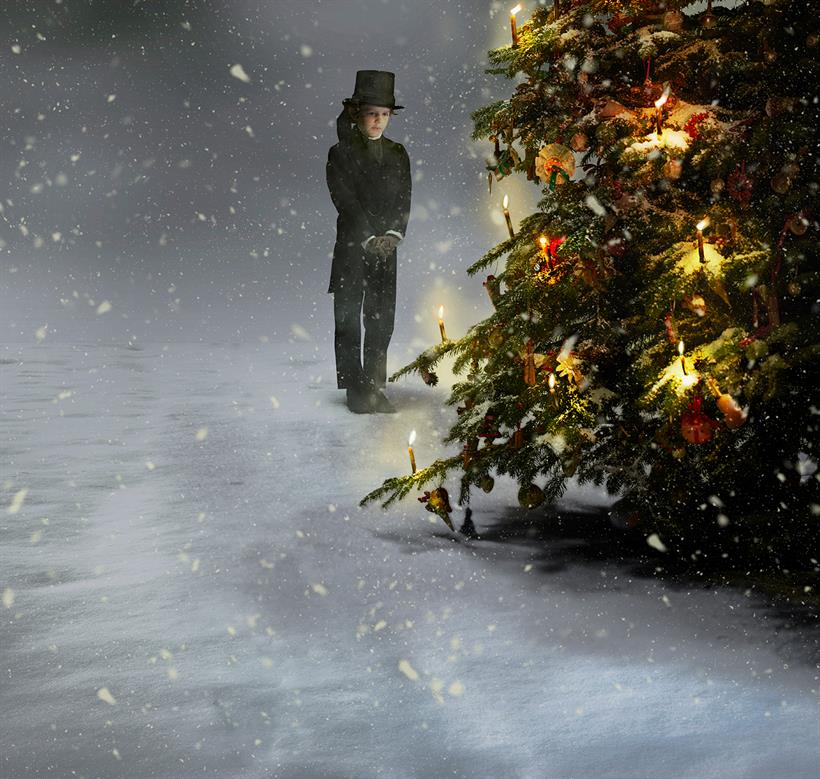 a snowy scene with a young boy in formal Victorian dress in front of a Christmas tree