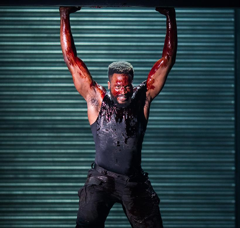 A man covered in blood holding up a metal shutter
