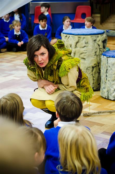 Trincula crouches down and talks to primary aged school children who are sitting on the floor in front of her
