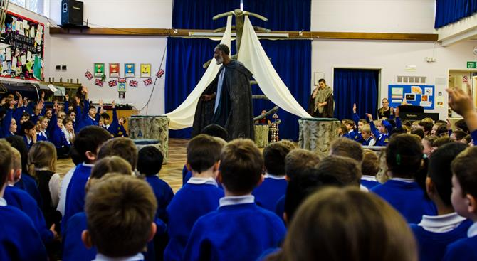 Prospero stands in front of the wreck of his ship with an audience of children