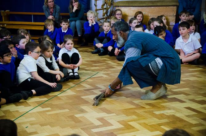 Prospero lays down his broken staff in front of entranced primary aged school children