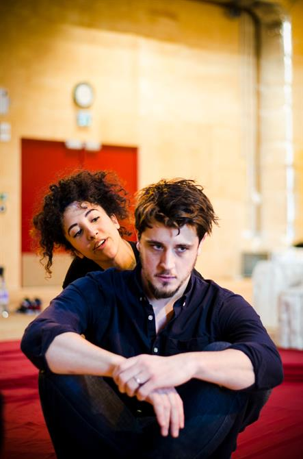 Sarah Kameela Impey and Oliver Towse in rehearsal  for First Encounters: The Tempest. Sarah Kameela Impey sits behind Oliver Towse and talks to him