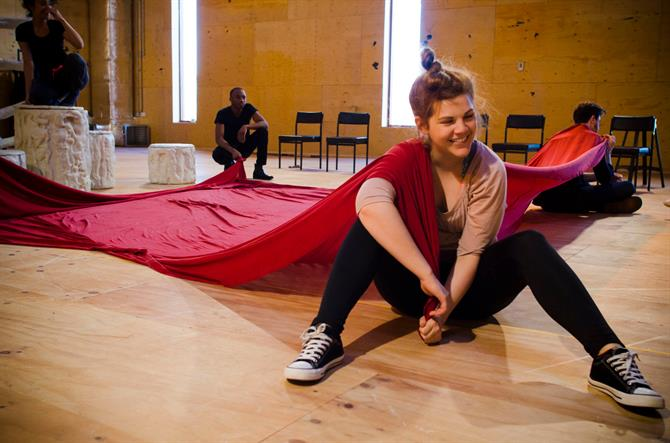 Alison Arnopp in rehearsal for First Encounters: The Tempest sitting on the floor with a red cloth across her right shoulder