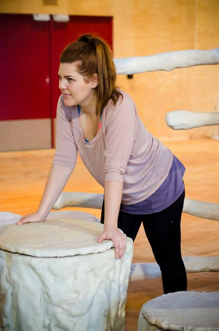 Alison Arnopp in rehearsal for First Encounters: The Tempest leaning down with both hands on a tree trunk