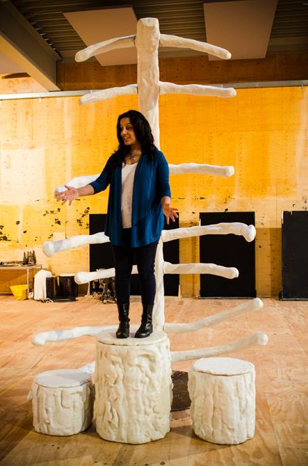 Director Aileen Gonsalves in rehearsal for First Encounters: The Tempest standing on a white log