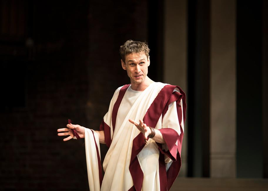 Martin Hutson as Cassisus in a white and red toga, gesticulating with his hands
