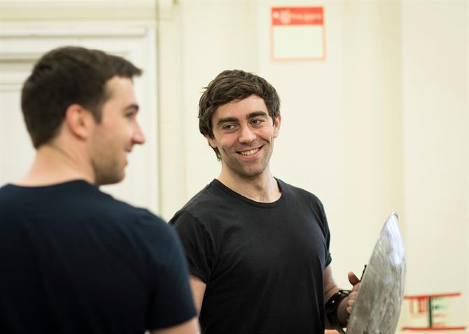 a man in a black t-shirt holding a shield smiles at the man next to him