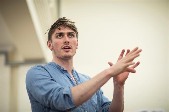 a man wearing a light blue shirt mid-speech