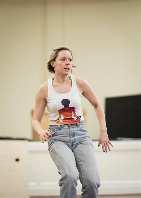 a woman in jeans and a white vest top mid movement