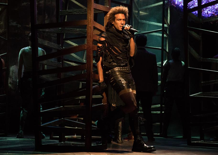 Man singing into a microphone, wearing a black leather dress, leaning against a scaffold