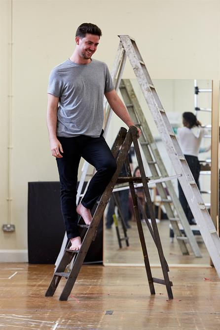 Robert Ginty standing on a ladder