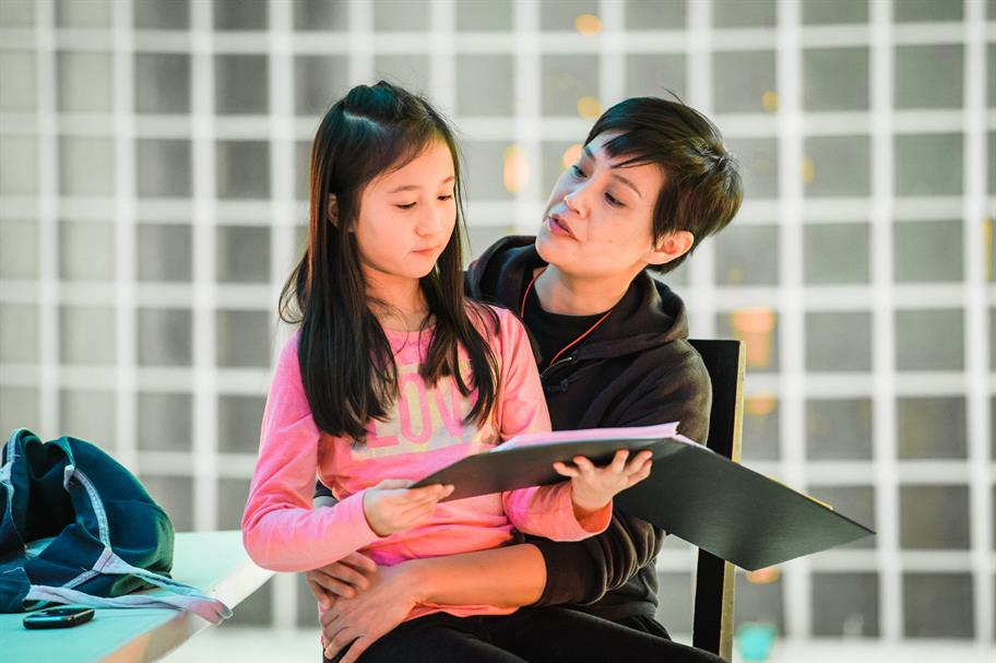 A girl sitting on a woman's lap reading from a black folder