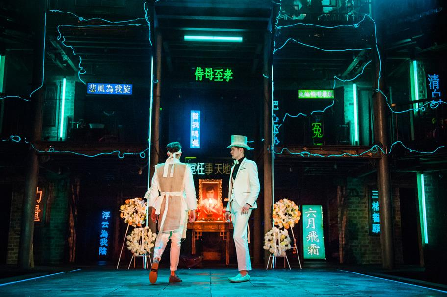 Two men in white suits stand in front of a neon-lit set with Chinese-language signs
