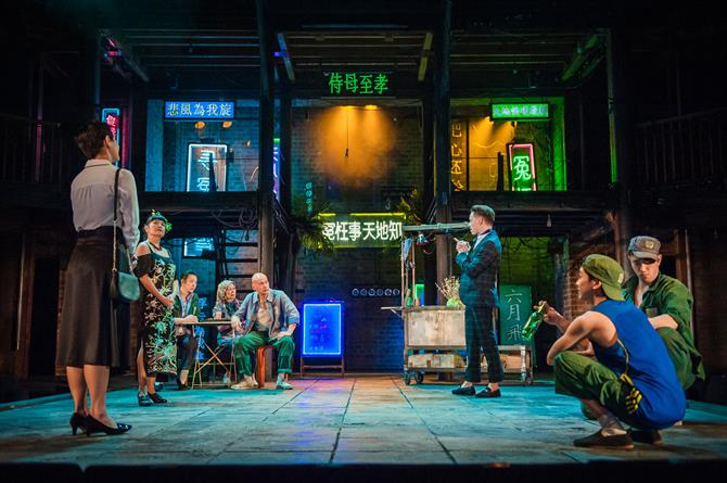The set of Snow in Midsummer, with brightly lit neon Chinese signs