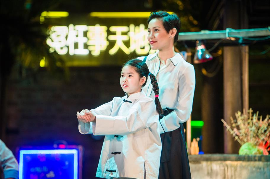 A small girl stands in front of a young woman. A large neon sign in Chinese symbols is behind them.
