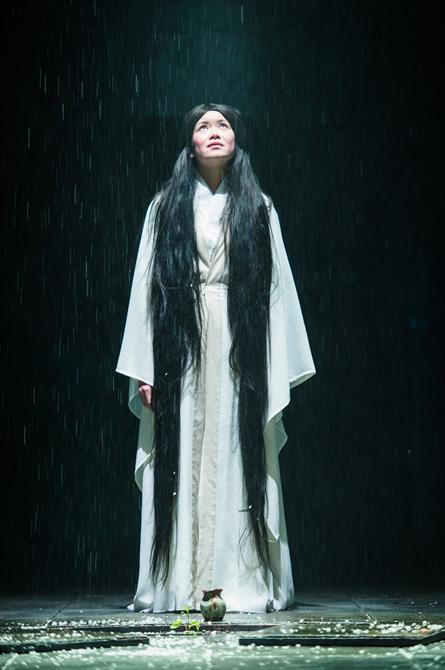 A young woman in a white robe with very long black hair gazes up at the sky as it rains