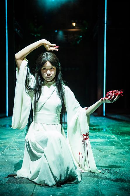 A woman in a white dress kneeling on the floor holding a bleeding human heart