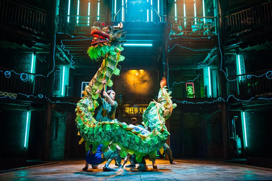 A green paper Chinese dragon is held up by actors on stage