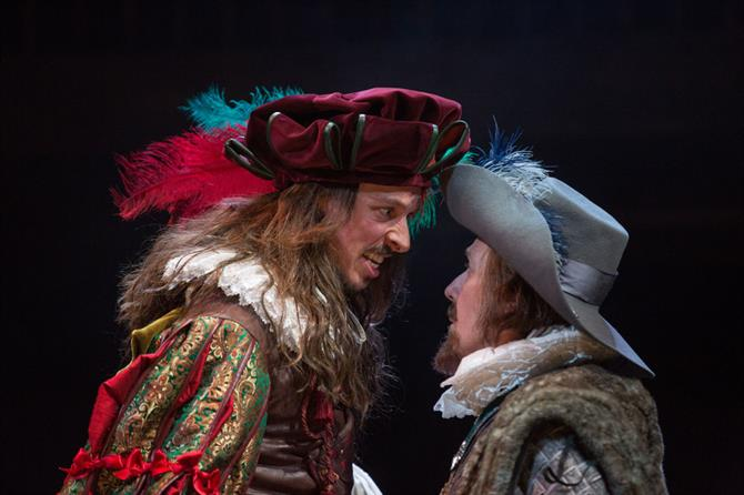 a man in a colour outfit with feathers in his hat stand face to face with another man - they look angry