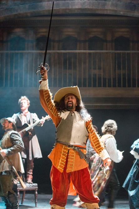 A man wearing an orange jacket, red trousers, a wide brimmed hat and a metal vest stands waving a sword in the air