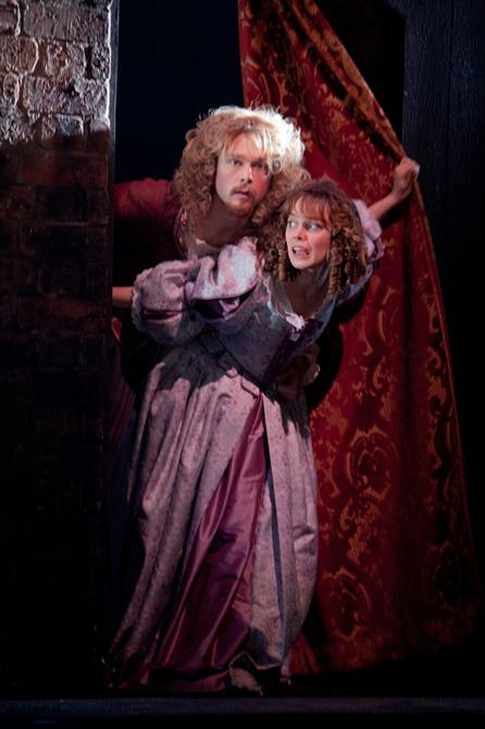 A man and woman pull back a curtain looking surprised