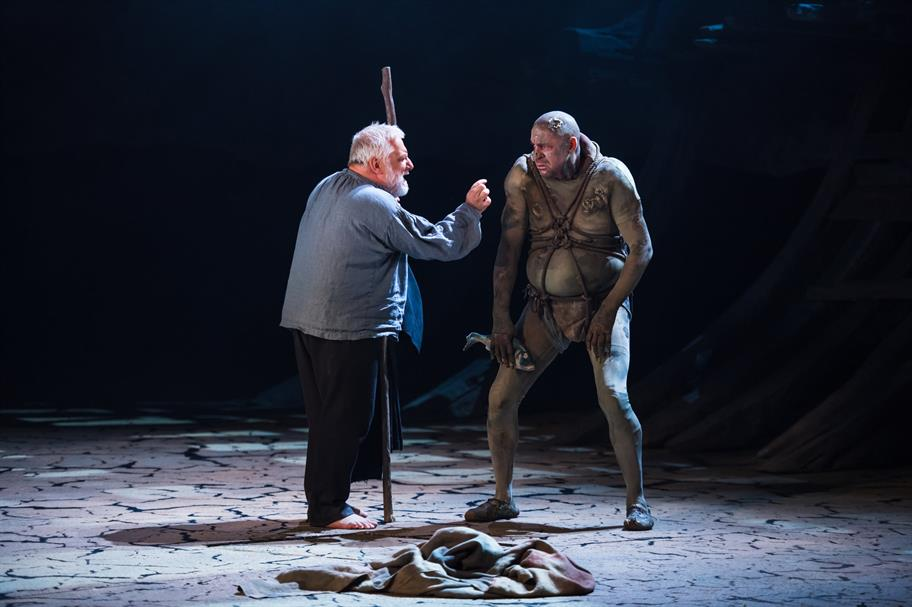 Prospero holds his staff and waves his hand at Caliban who's clutching a fish