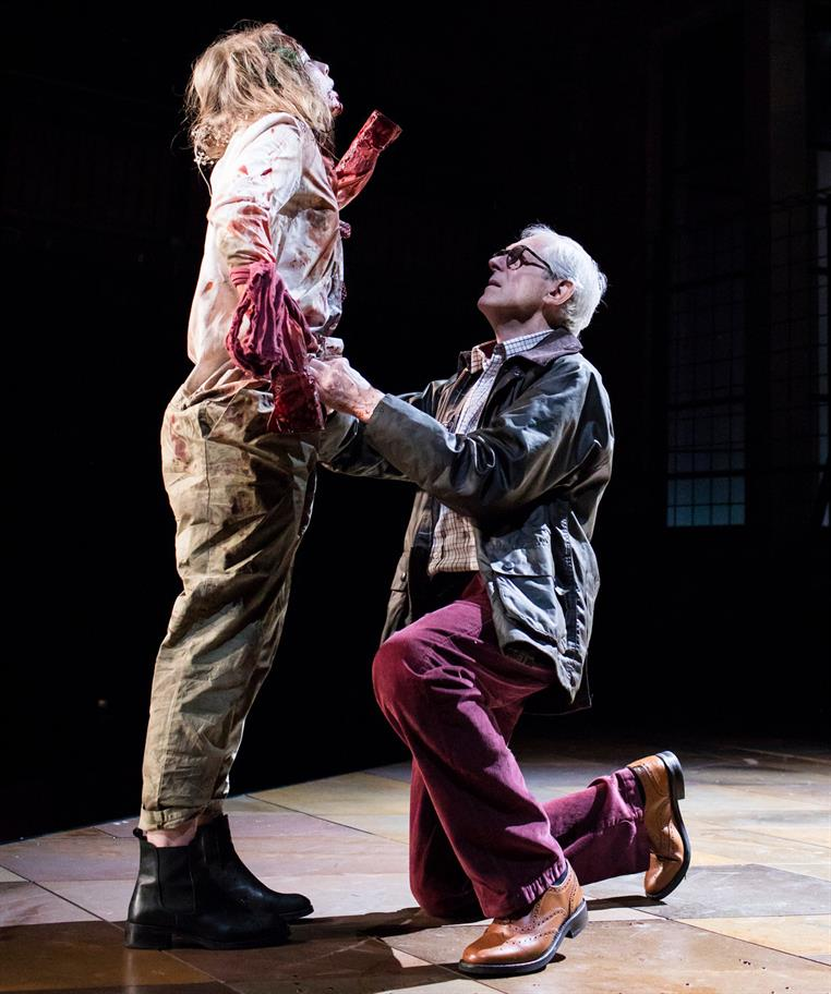 An older man kneels in front of a young woman with bloodied arms and missing hands.