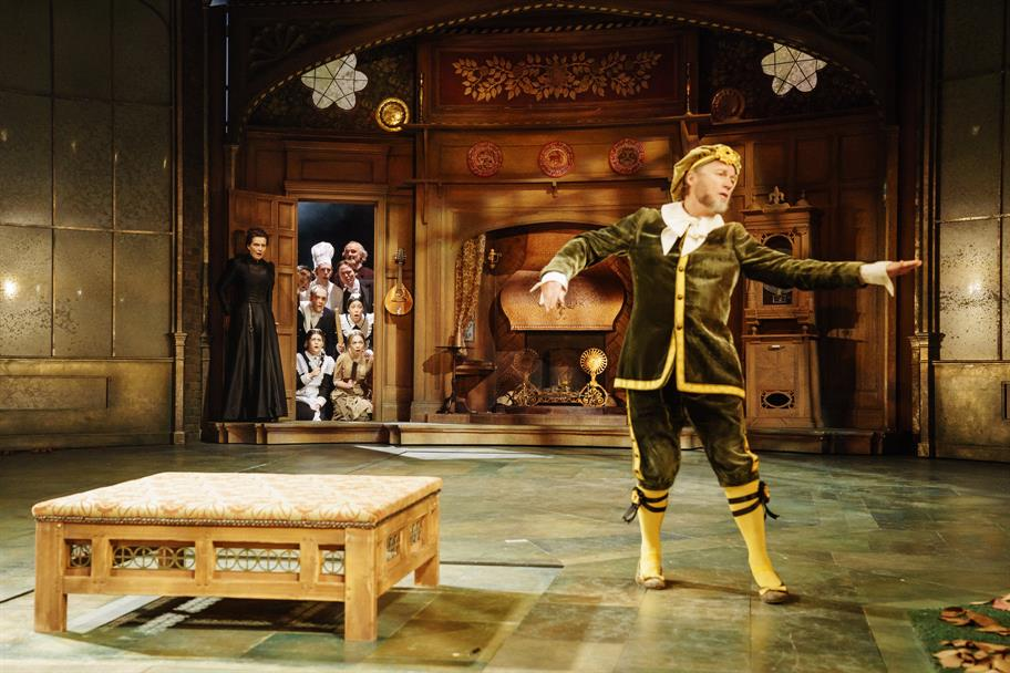 Malvolio in yellow stockings and a green velvet suit capering about watched by Olivia and her servants