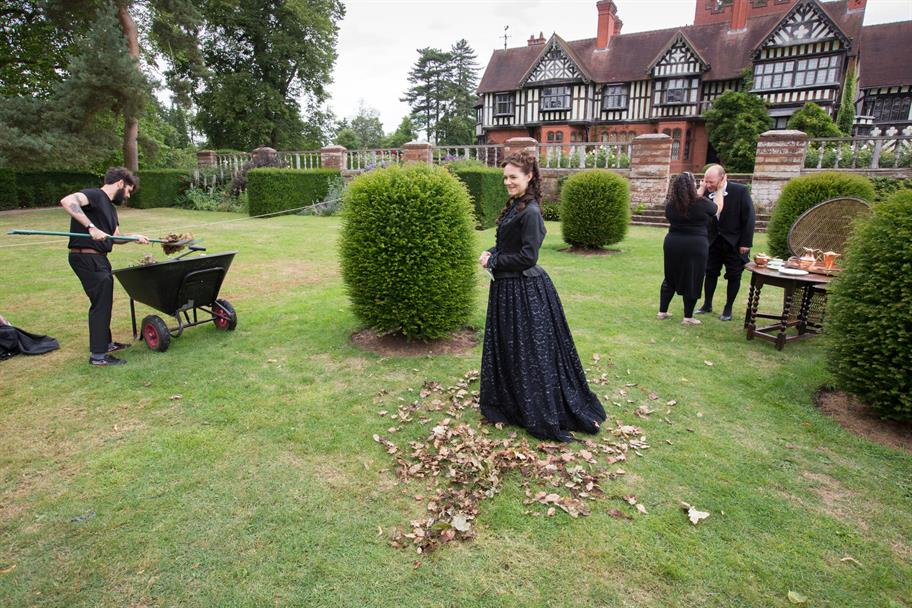 A woman in black in a garden, surrounded by autumn leaves