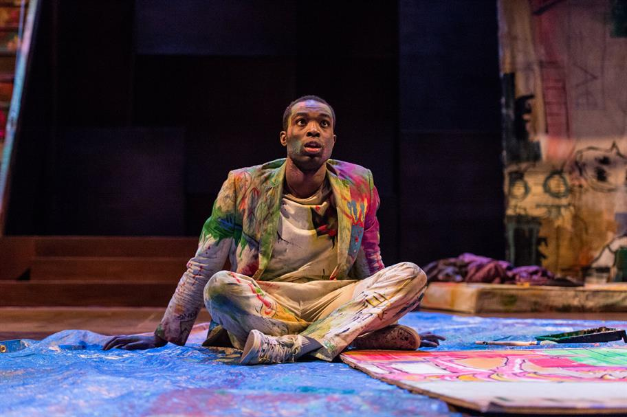 Paapa Essiedu as Hamlet seated cross legged on the floor in a white suit covered in paint, looking up