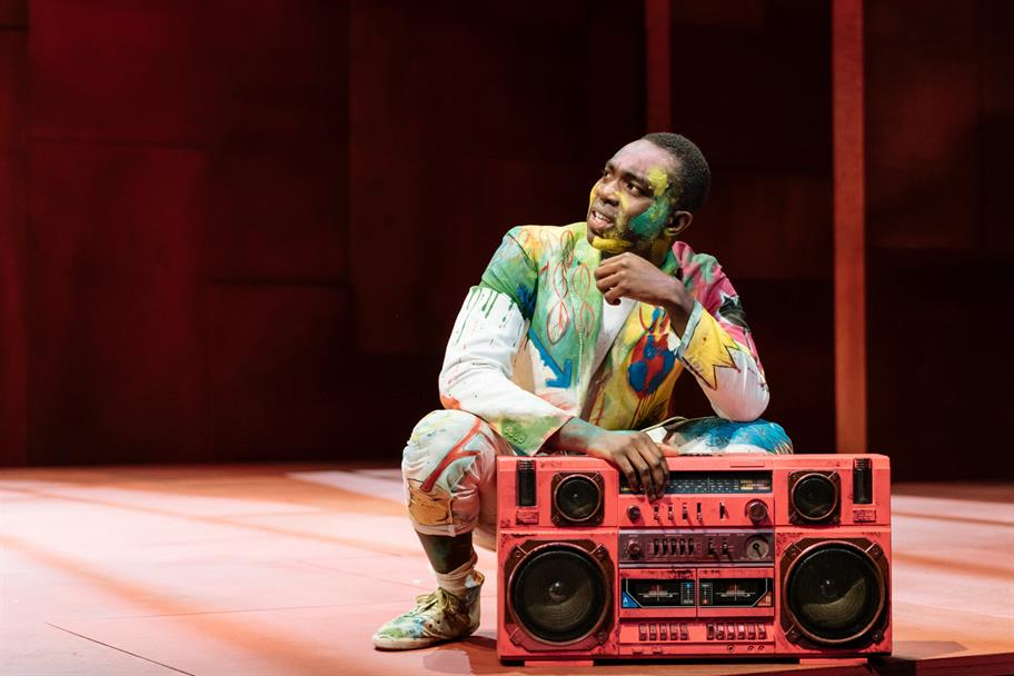 A man in colourful dress and covered in paint crouches beside a large stereo.