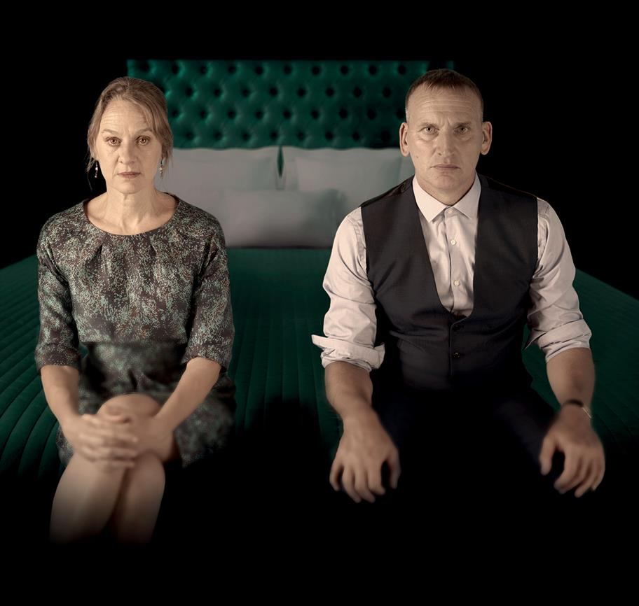 Niamh Cusack and Christopher Eccleston sit on the edge of a luxurious bed