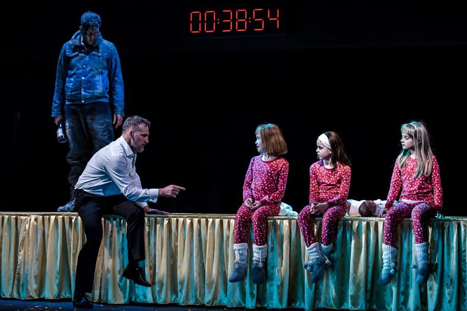 Christopher Eccleston perched on the edge of a stage talking with pointed finger to three small girls in red spotty pyjamas perched on the stage
