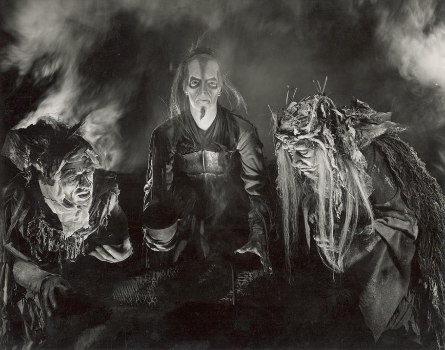 Black and white image of three hagged and ugly witches, surrounded by smoke.